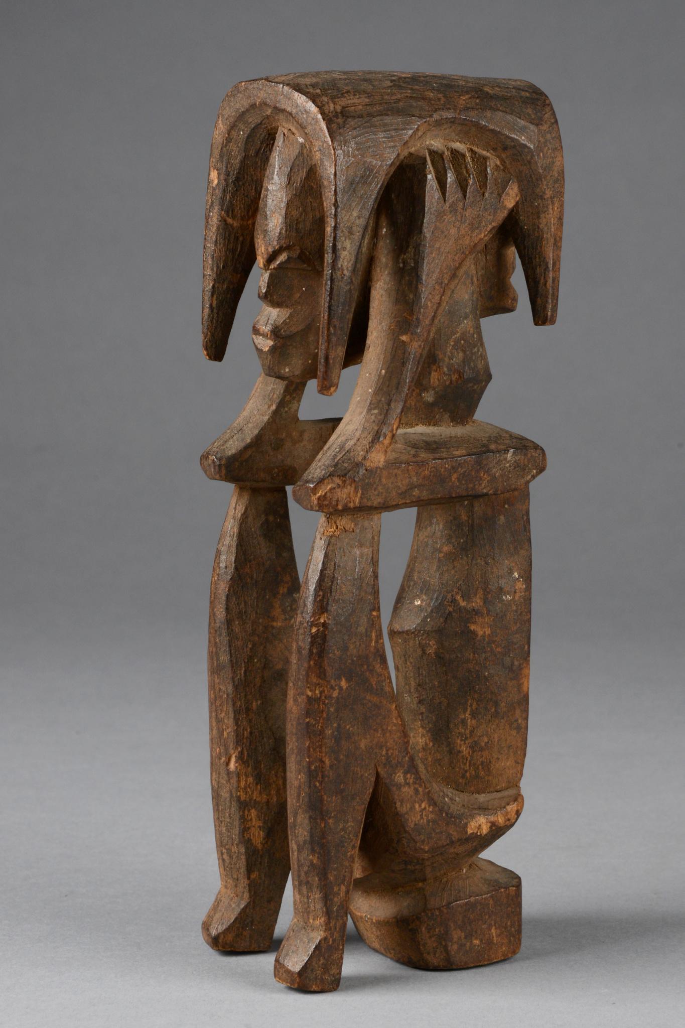 Sitzende janusköpfige Figur