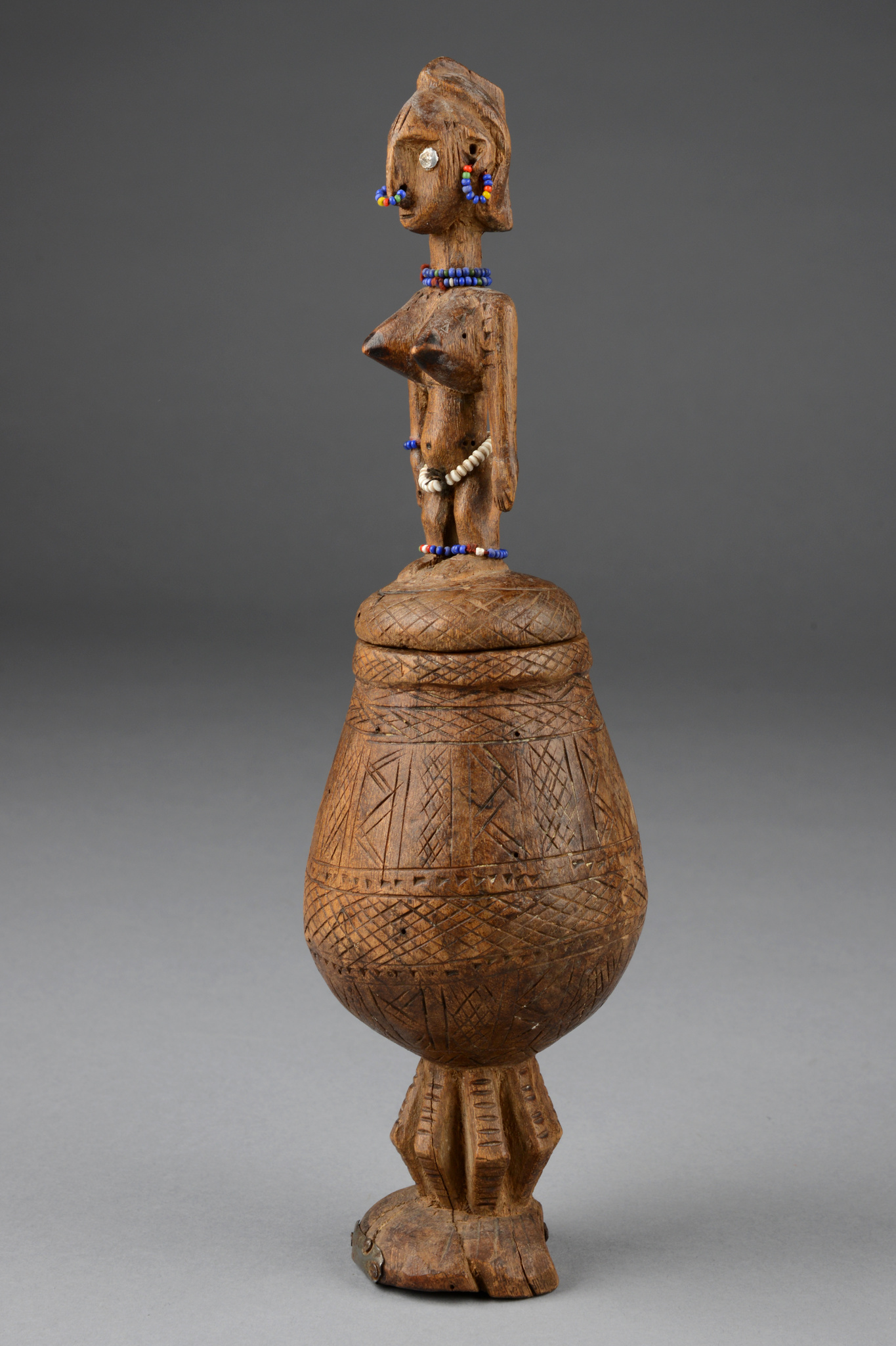Container with figurally carved lid