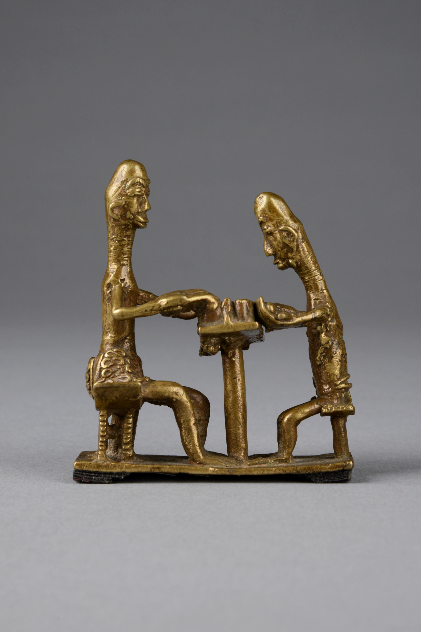 "Goldweight: two people playing the bean game ""mancala"""